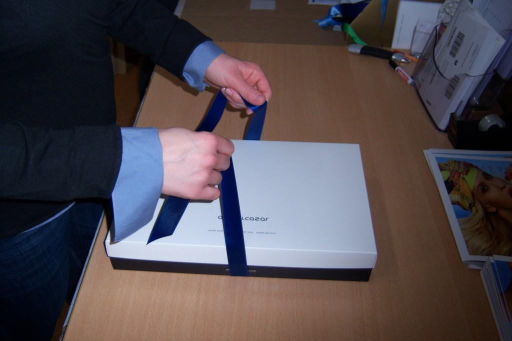 Corina bindet die Seidenschleife vom ana alcazar Paket